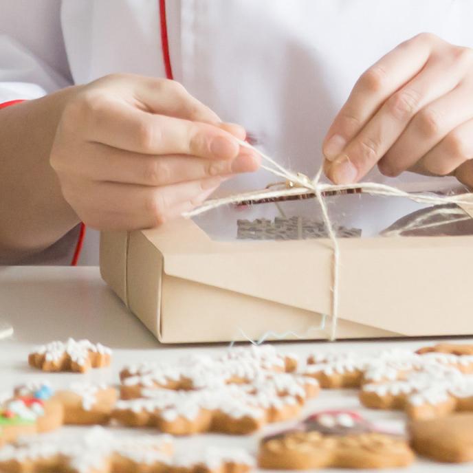 Pasticcere che annoda nastro su scatola per biscotti